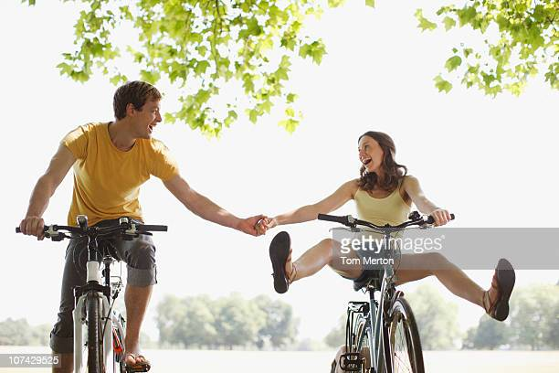 happy couple riding bicycles and holding hands - benen gespreid stockfoto's en -beelden