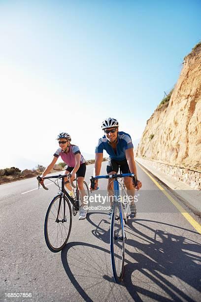 Glückliches Paar Reiten Fahrräder in einer mountain road