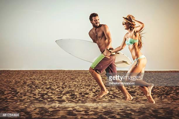 幸せなカップルはビーチでのランニング