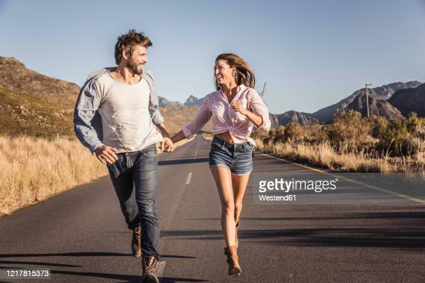 happy couple running on a country road - 日常から抜け出す ストックフォトと画像