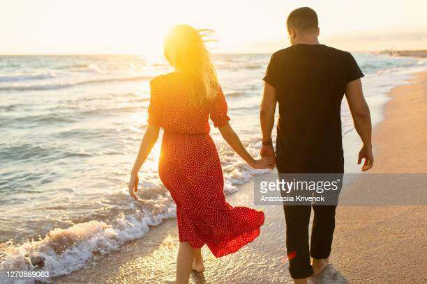 happy couple running on the beach. - red dress stock pictures, royalty-free photos & images
