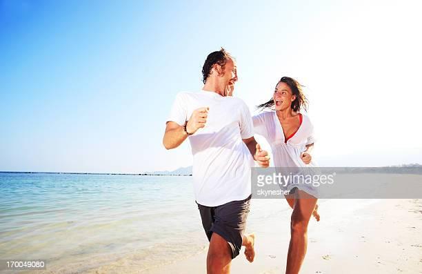 casal feliz correr na praia. - homem pegando mulher imagens e fotografias de stock