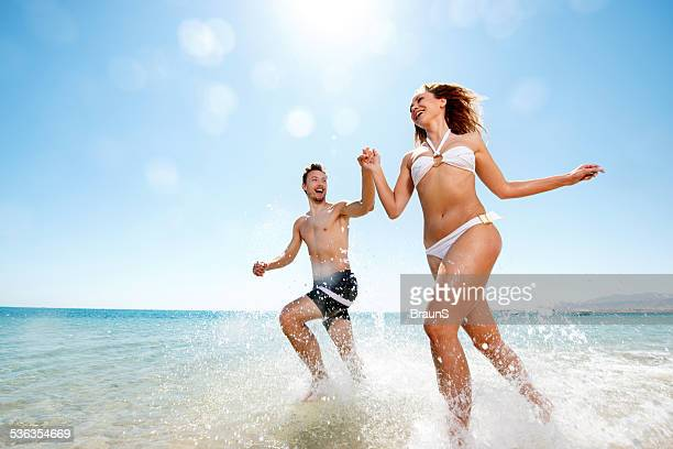 Happy couple running through sea.