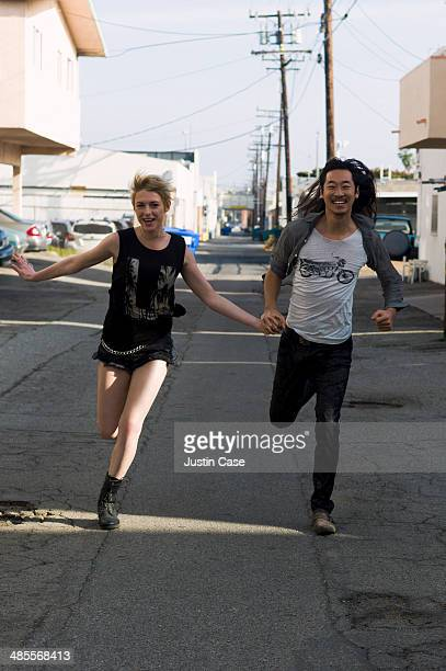 happy couple running together is the street