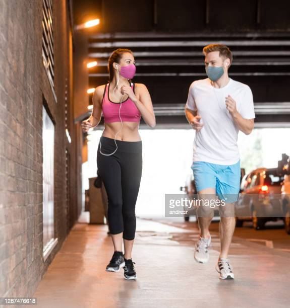 happy couple running together wearing facemasks during the covid-19 pandemic - state of emergency stock pictures, royalty-free photos & images