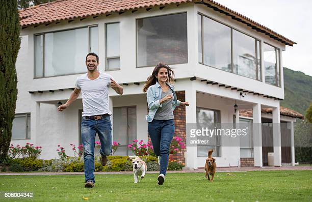 Happy couple running with their dogs