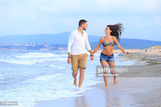 Happy couple runs through waves on sand