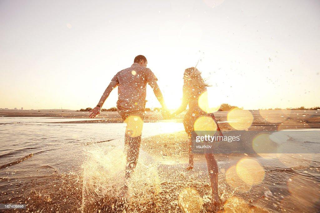 A happy couple runs through waves on sunlit beach : Stock Photo