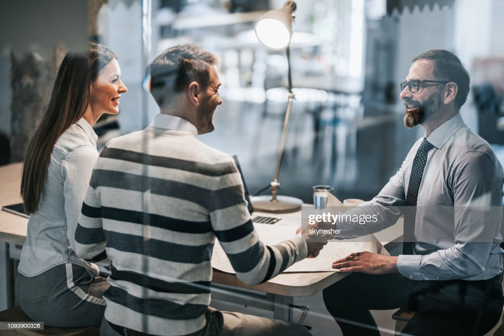 Happy couple shaking hands with real estate agent in the office. : Stock Photo