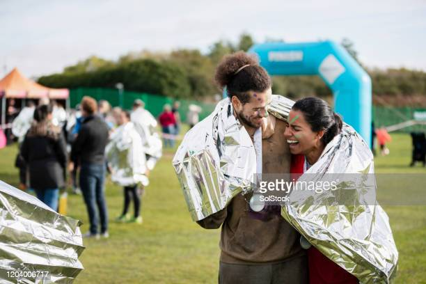 happy couple sharing foil blanket after stampede race - medallist stock pictures, royalty-free photos & images