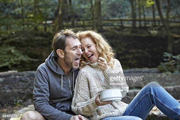 happy couple sharing food outdoors - man eating woman out stock-fotos und bilder
