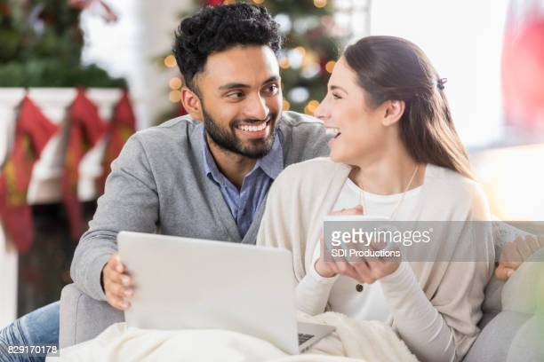 Happy couple shop online for Christmas presents