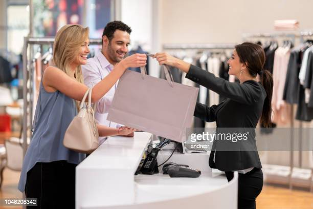 happy couple shopping at a clothing store - cashier stock pictures, royalty-free photos & images