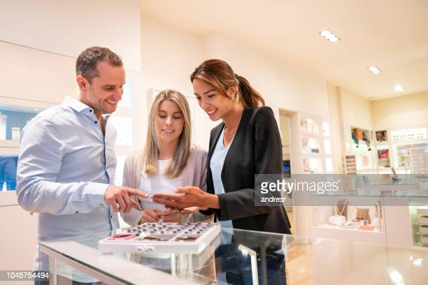happy couple shopping at the jewelry store - jewelry store stock pictures, royalty-free photos & images