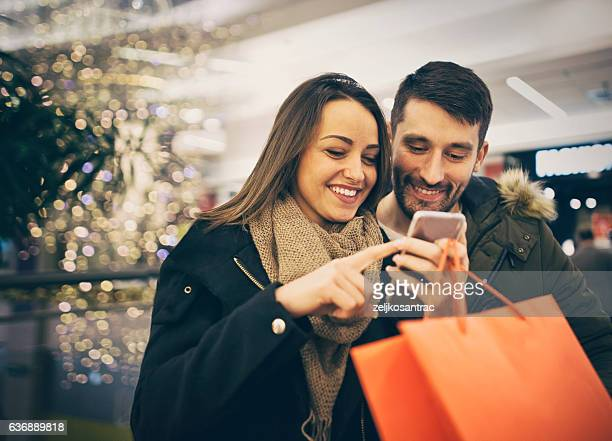 Happy couple shopping in the city with smartphone