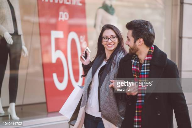 happy couple shopping on sale - black friday stock photos and pictures