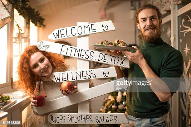Happy couple showing healthy food in a restaurant.