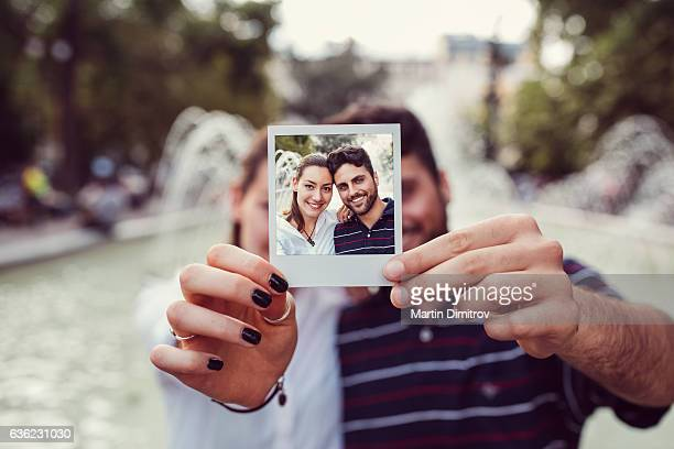 Happy couple showing instant selfie
