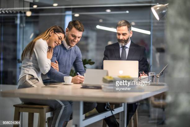happy couple signing a contract on a business meeting with their insurance agent. - lease agreement stock photos and pictures