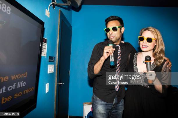 happy couple singing karaoke while standing in nightclub - duet stock pictures, royalty-free photos & images