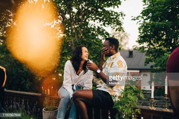 happy couple siting on railing in backyard during social gathering - hands covering mouth stock pictures, royalty-free photos & images