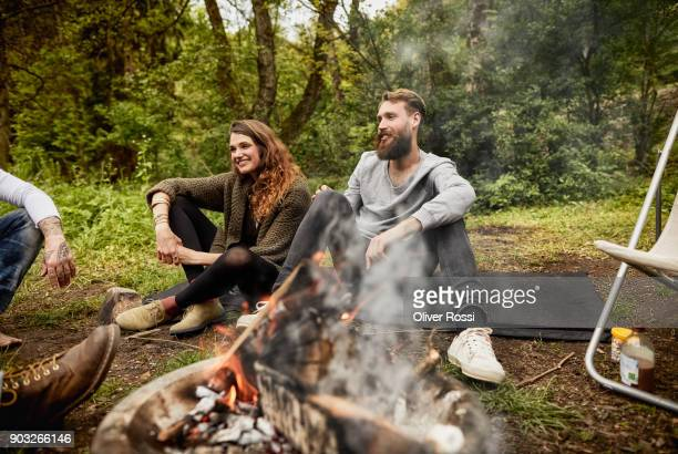 happy couple sitting at campfire with frineds - simple living stock pictures, royalty-free photos & images