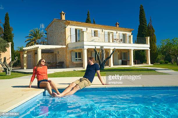 happy couple sitting at pool of rural estate