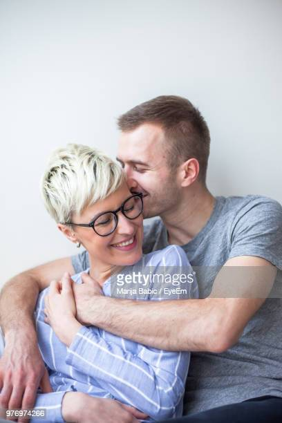 happy couple sitting by wall at home - marija mauer stock-fotos und bilder