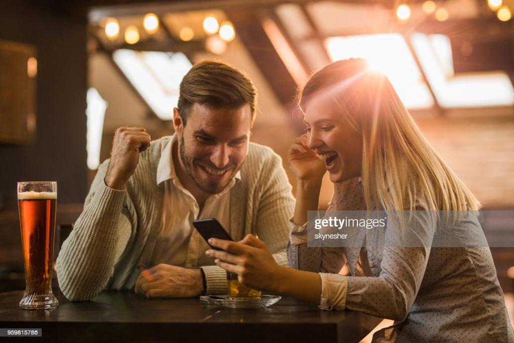 Glückliches Paar in einem Café sitzen und lesen eine überraschende SMS auf Handy. : Stock-Foto