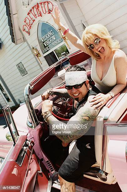 Happy Couple Sitting in a Convertible Outside a Church