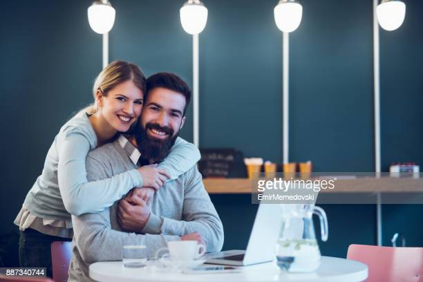 Happy couple sitting in cafe with laptop and web surfing