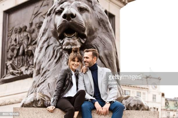 brautpaar sitzt vor löwendenkmal am trafalgar square in london - izusek stock-fotos und bilder