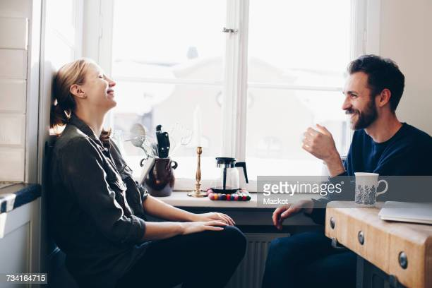 Happy couple sitting in kitchen against window at home