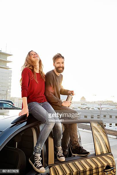 Happy couple sitting on car roof