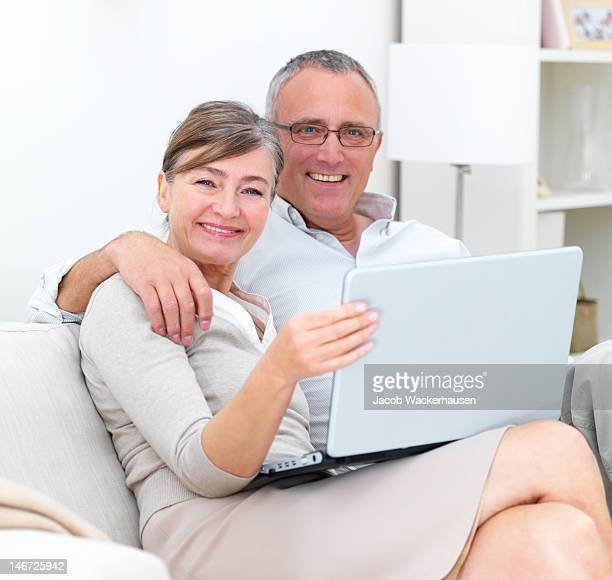 Happy couple sitting on couch with laptop