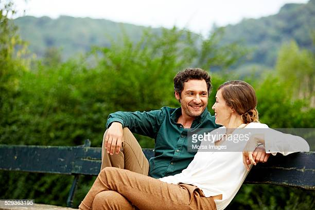 Happy couple sitting on park bench