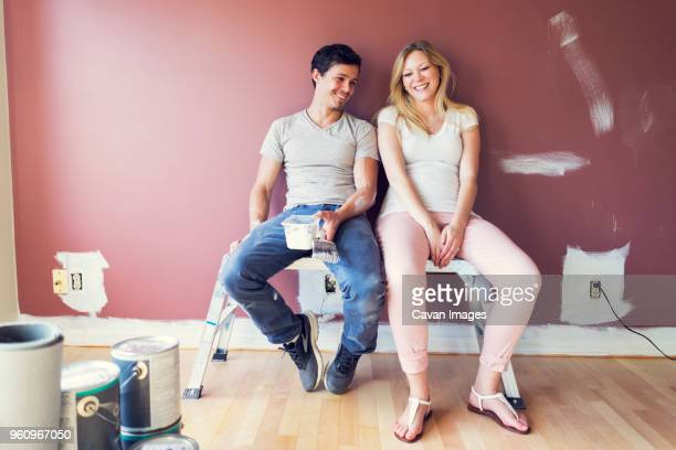 Happy couple sitting on stool against wall at home
