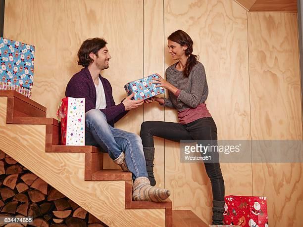 happy couple sitting on wooden stairs holding christmas presents - gift lounge stock-fotos und bilder