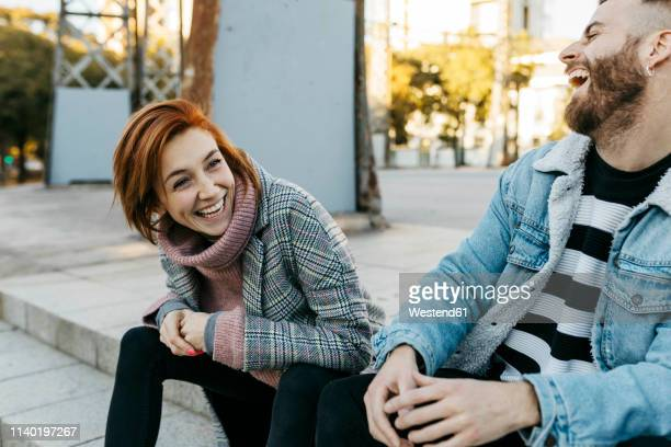 happy couple sitting outdoors laughing - ungestellt stock-fotos und bilder