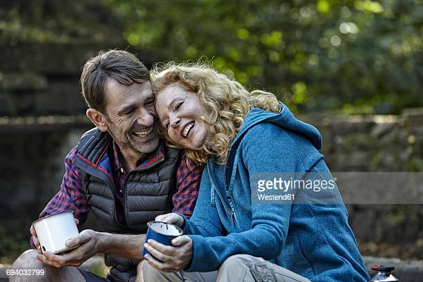 Happy couple sitting outdoors with coffee mugs