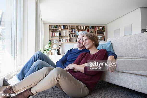 Happy couple sitting side by side on the floor of their living room