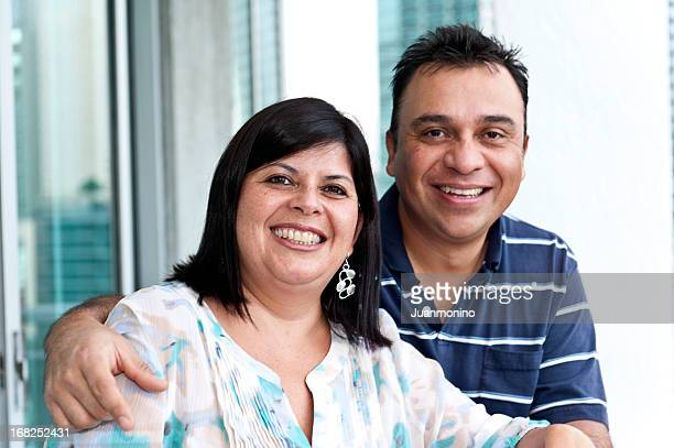 happy couple smiles in front of a bright window - fat woman sitting on man stock pictures, royalty-free photos & images