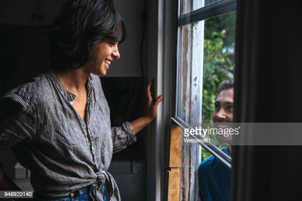 happy couple smiling at each other through the window - femme entre deux hommes photos et images de collection
