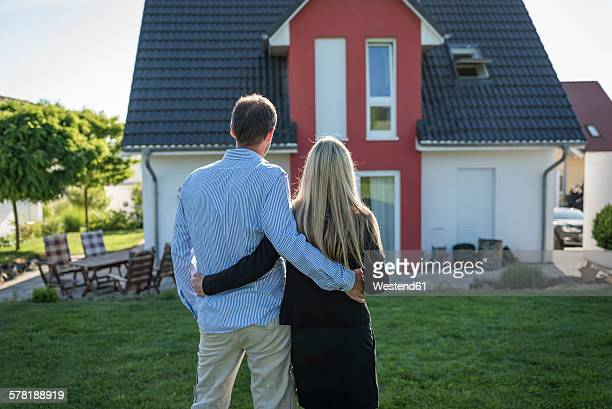 Happy couple standing arm in arm in the garden looking at their house