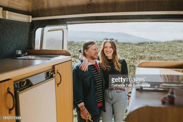 happy couple standing at the rear of a retro camper van - human relationship stock pictures, royalty-free photos & images