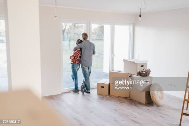 Happy couple standing at window of their new home