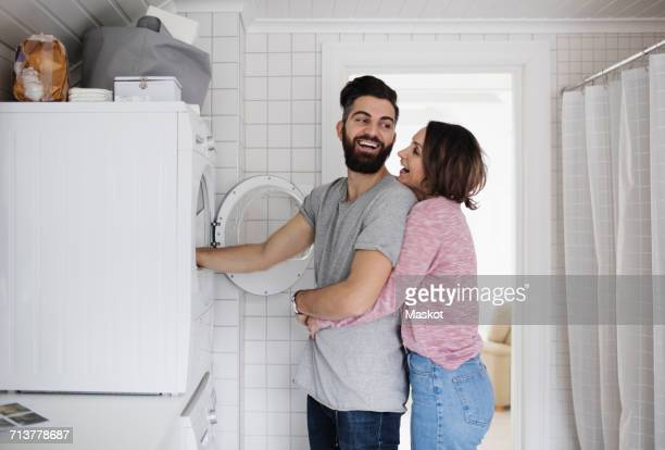 happy couple standing by washing machine at home - waschen stock-fotos und bilder