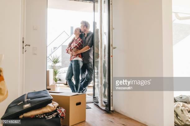 Happy couple standing in door of their new home