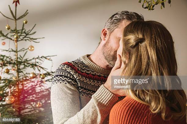 Happy couple standing in front of Christmas tree, kissing under mistletoe