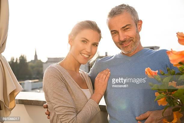 Happy couple standing on balcony, arms around